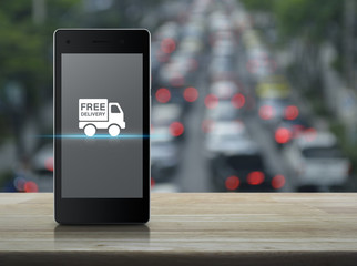 Free delivery truck icon on modern smart phone screen on wooden table over blur of rush hour with cars and road, Transportation business concept