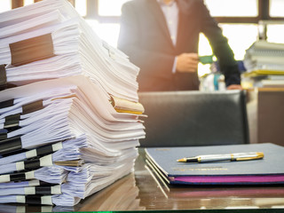 Close up of business documents stack on businessman background