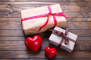 Gift boxes with present  and red shiny hearts on vintage wooden
