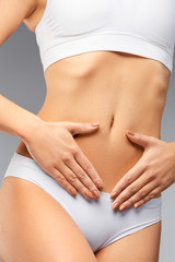 Closeup Of Beautiful Woman With Slim Body Holding Hands On Belly