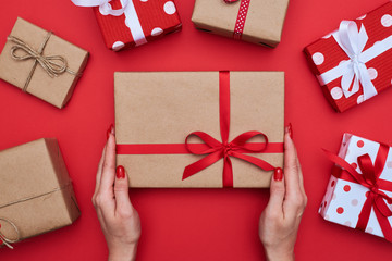 Decorated present with red ribbon in woman hands