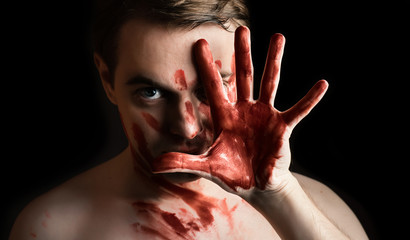 Portrait of young man with blood on his face and palm on dark ba