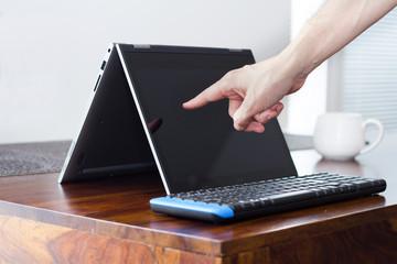 finger touching laptop tablet