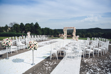 White chairs stand around path to wedding altar