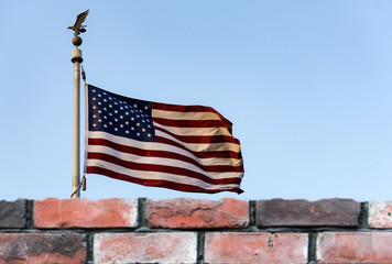 American flag and defocused brick fence, the United States confrontation and refugees