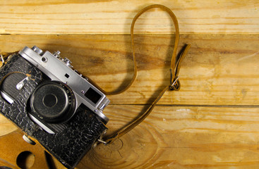 Old retro camera in leather case on wooden background