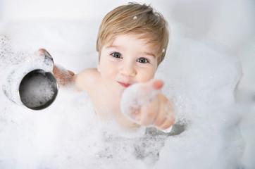 Obraz small child takes a bath with foam - fototapety do salonu