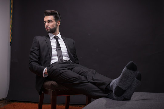 one young man sitting chair relaxing socks suit