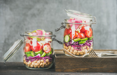 Healthy take-away lunch jars. Vegetable and chickpea sprout vegan salad in glass jars, grey concrete wall background, copy space, selective focus. Clean eating, vegetarian, raw, detox, dieting concept