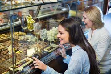 Cheerful smiling female friends selecting fine chocolates and co