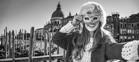 woman in Venice, Italy taking selfie while in Venetian mask