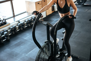 Fitness woman working out on spinning bicycle in gym