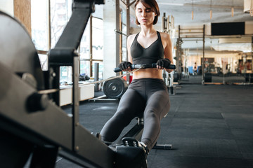 Fitness woman working out using exercise equipment in gym