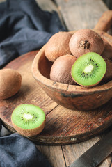 Organic fresh kiwi fruit on a wooden cutting board and utensils. rustic style. close up and selective focus
