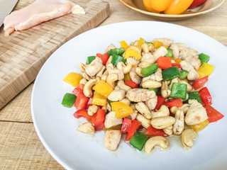 Fried chicken with cashew nuts and bell pepper on white plate on wood table.
