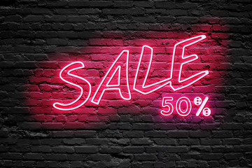 SALE 50 % Percent. fluorescent Neon tube Sign on dark brick wall. Front view. Can be used for online banner ads or background. night moment.