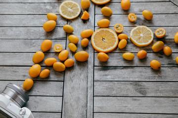 Camera and mixed fruits: Kumquat, oranges, lemons on wooden boar