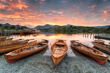 Fototapete - A fiery sunset over boats on the shore of Derwentwater at Keswick in the Lake District in Cumbria