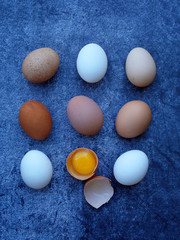 composition of fresh farm white and brown eggs on dark background