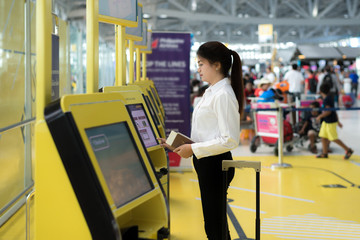 Young Asian businesswoman using self check-in kiosks in airport.