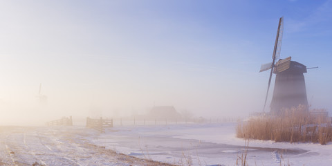 Wall Mural - Dutch windmill in a foggy winter landscape in the morning