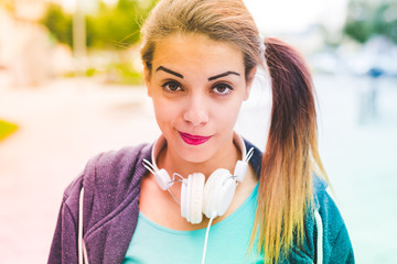 Half length of young beautiful mixed race woman listening music with headphones looking in camera smiling - relaxing, serene, music concept