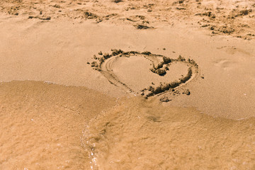 Heart drawn on the sand at the beach. Figure heart for you.