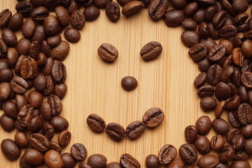 A smile face made from coffee beans on a bamboo background