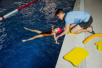 Swimming coach teaches the girl to keep the balance in the water. child floating in the pool
