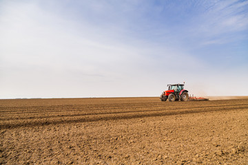 Wall Mural - Farmer in tractor preparing land with seedbed cultivator
