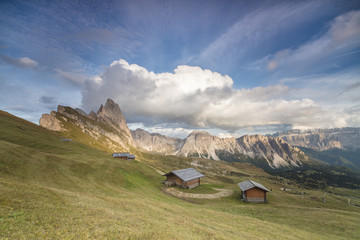 Sunset on the green meadows and huts of the Odle mountain range seen from Seceda, Val Gardena, Trentino-Alto Adige, Italy, Europe