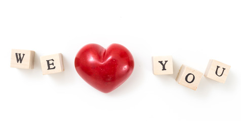 Red heart and wooden cubes with We and You, on white background. We love you concept.