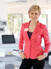 Happy businesswoman standing at trendy home