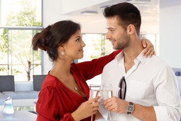 Happy romantic young couple with champagne at home