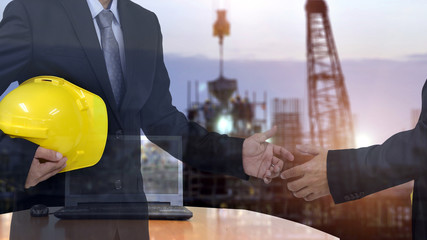 Two Businessman  handshake for Safety Construction Concept , and construction site background.