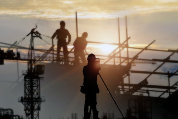 Silhouette structural steel beam build large residential buildings at construction site .