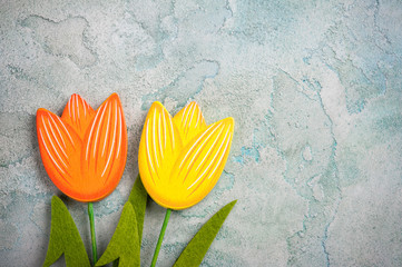 Wooden tulips on blue concrete weathered background