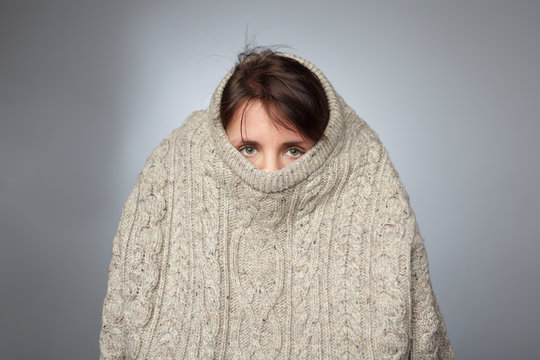 Girl pulls a large knitted sweater over her head.