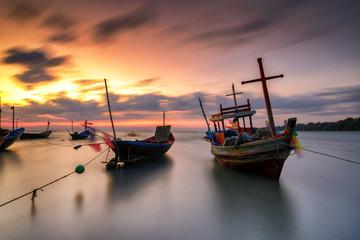 Fisherman wooden boat on beach sunset Thailand.
