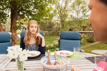 Teenage girl talking to father at table in yard