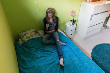 High angle view of teenage girl using smart phone while sitting on bed at home