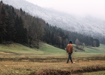 Austria, Mondsee, back view of young man strolling in autumn