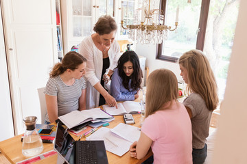 Woman assisting teenage girls in doing homework at home