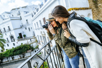 Two young women in a town taking pictures with a camera