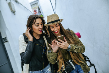 Two young women in a town looking at cell phone