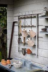 Garden tools and flower pots hanging on wall