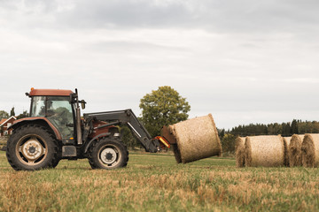 Farmer arranging hay bales by using tractor at farm against sky