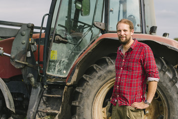 Portrait of smiling farmer standing against tractor at farm