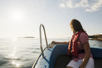 Woman sitting on motorboat in Baltic Sea while looking at sea