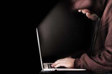 Male computer hacker wearing a hooded top leaning over a laptop in the dark. The screen light illuminates the man with a beard performing illegal activities. Black copy space on the left Wall mural